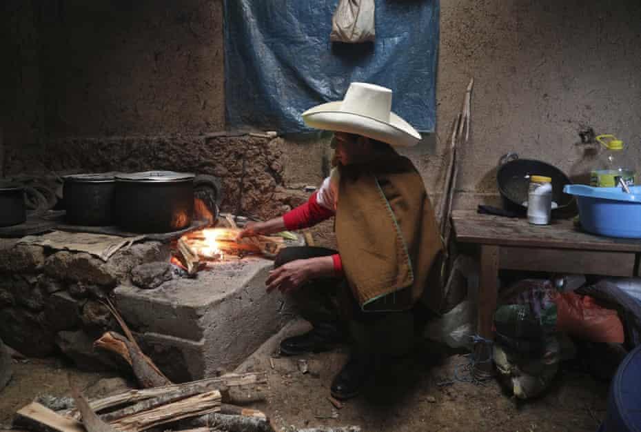 Pedro Castillo cooks breakfast for his family in his home in Chugur, Peru.