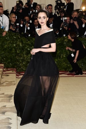 Lily Collins steered clear of the angelic look and went for something darker with her sheer Givenchy gown and Gothic make up, while clutching rosary beads.