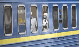Medical workers are reflected in the windows of a carriage