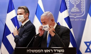 Greek prime minister Kyriakos Mitsotakis and Israel's prime minister Benjamin Netanyahu wear face masks with both countries' flags after a press conference on 8 February.