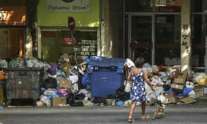 A woman walks past the mounds of rubbish due in Athens, Greece on 29 June