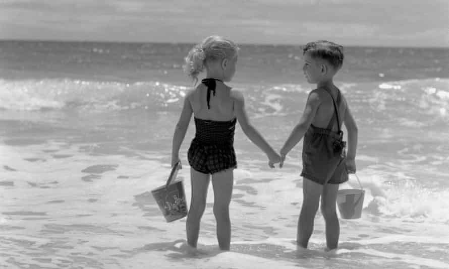 two children holding hands on the beach