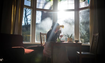 Young woman sat by a window with daffodils