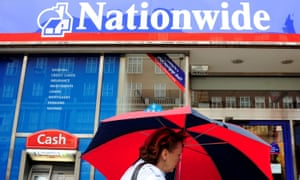 A woman holding an umbrella walks past a Nationwide branch