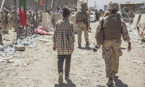 A marine escorts a young woman at an evacuation control checkpoint at Hamid Karzai International Airport in Kabul, Afghanistan, Thursday, 26 August 2021.