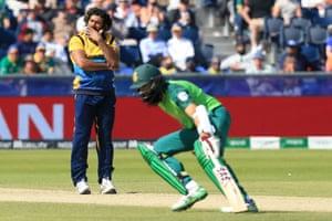 Malinga watches on as Amla runs a single for his half century.