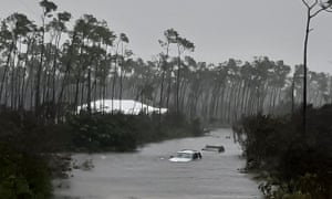 Rising waters cover cars on a road in Freeport on Tuesday.