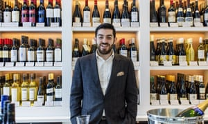 Zack Charilaou stands in front of shelves full of wine