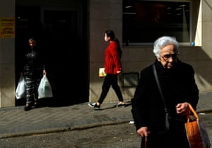A woman wearing a surgical mask arrives to do the shopping at a supermarket at the Usera neighbourhood in Madrid
