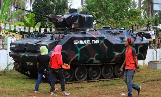 Residents walk past a tank outside a polling station in the town of Pantar, in Mindanao, on 9 May as people vote in the Philippines' presidential election.