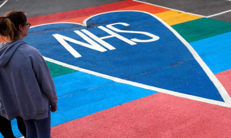 People look at a hand-painted tribute sign to the NHS.