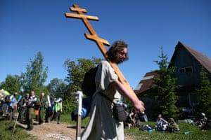 A pilgrim carries a cross