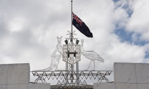 Coat of arms and Australian flag atop Australian Parliament House in Canberra.