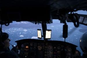 A helicopter flies over hundreds of icebergs floating near the Helheim glacier.