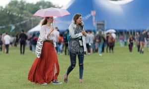 Festivalgoers shelter from the rainy weather