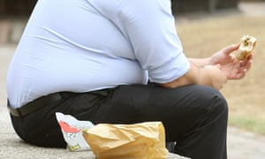 An overweight man sitting on the edge of a wall.