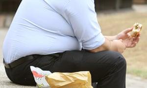 An overweight man eating.