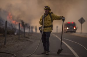 A firefighter holds a hose on the 120 freeway during the La Tuna Fire near Burbank, California.