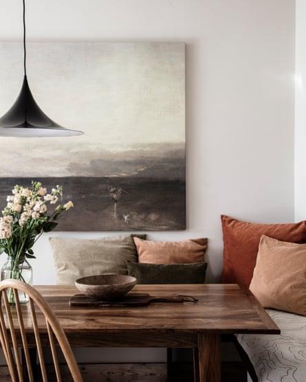 Velvet cushions around the walnut dining table.