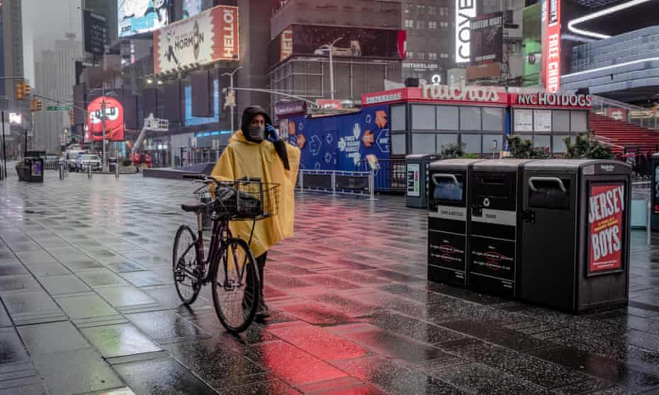A lone person walks through Time Square in New York City on 29 March 2020.