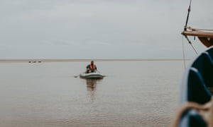 Chef Charlie Hodson takes food supplies and cooking utensils to the sandbank in a dinghy.