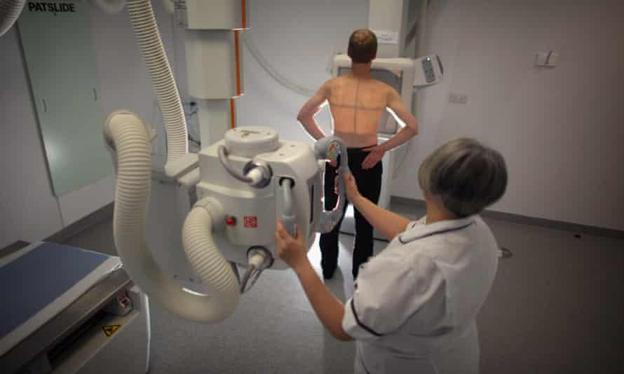 A patient (posed by a model) is given an X-ray.