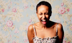 A woman screaming against a pastel wallpaper background