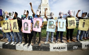 Protesters hold banners reading 'Take care of the Earth' at a street in Banda Aceh, Sumatra, Indonesia