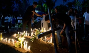 Relatives light candles for people who died during the bomb blast at St Sebastian's church in Negombo, Sri Lanka
