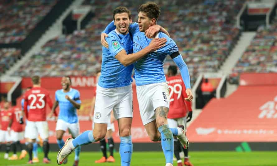John Stones (right) celebrates with Rúben Dias after scoring for Manchester City in their Carabao Cup semi-final win at Manchester United.
