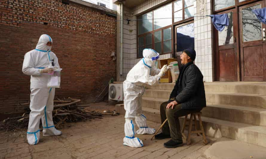 A medical worker collects nucleic acid sample for a villager at Shizhuang Village in Yuanshi County of Shijiazhuang City