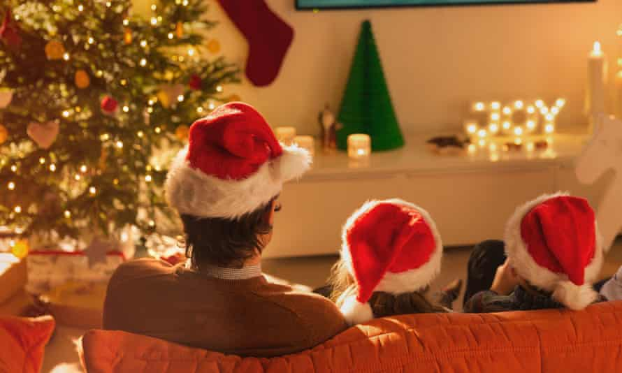 A family in Santa hats watching Christmas television