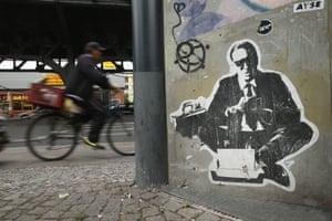 A man on a bicycle rides past street art in Skalitzer Straße, Kreuzberg.
