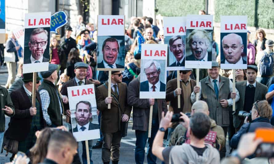 Demonstrators carry placards labelling politicians including Boris Johnson and Nigel Farage as liars.