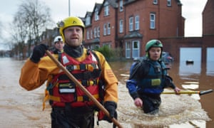 Rescue workers walk along a flooded road in Carlisle after Storm Desmond in December.