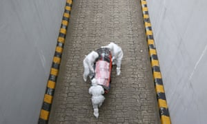 Health workers wearing protective suits move a Covid-19 patient in an isolation stretcher from an ambulance to a hospital in Seoul.