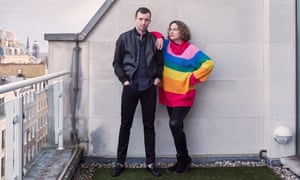Sophie Heawood in a bold stripey jumper leaning an arm on the shoulder of life coach Michael Serwa on the roof of his Mayfair penthouse.