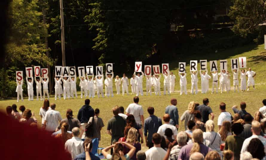 Cult members in white holding signs that read 'stop wasting your breath'