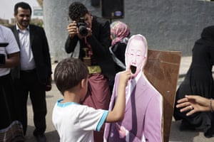 A young boy drops a Yemeni riyal into the hollowed-out mouth of a cardboard figure of then-UN secretary general Ban Ki-moon at a demonstration led by Yemeni mothers outside the UN offices in Sana'a in June 2016.
