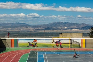 Children play at Jalousie's main sports arena, against a backdrop of the mountains that surround Port-au-Prince