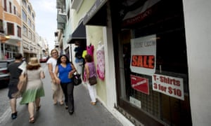 People walk past a closed store in San Juan, Puerto Rico.