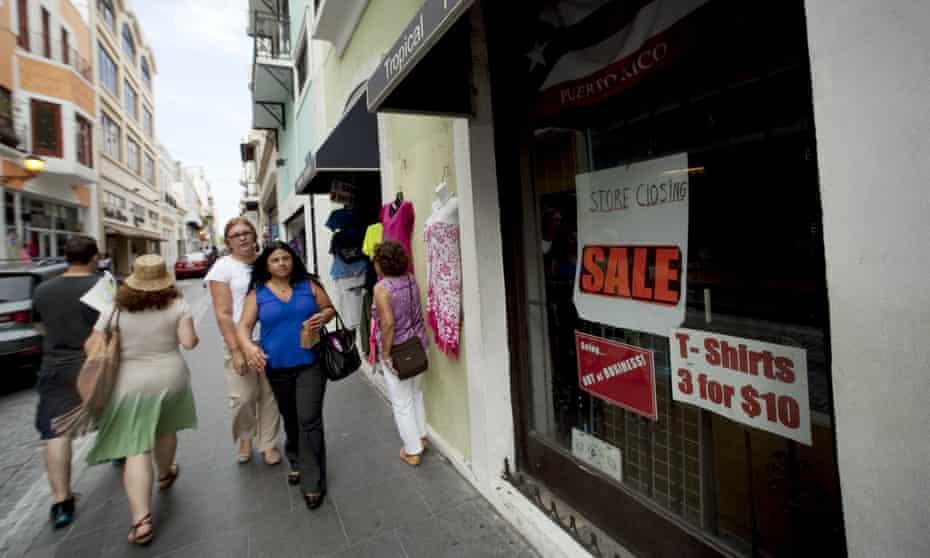 People walk past a closed store in San Juan, Puerto Rico.