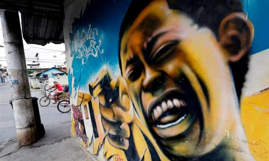 Graffiti depicting a laughing man with a gun inside the Cidade de Deus favela.