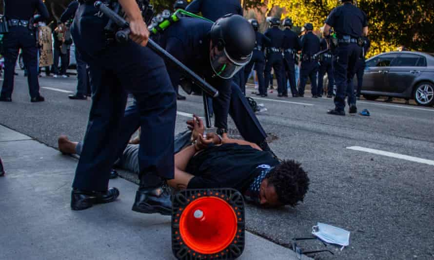 A police officer arrests a man during a protest demanding justice for George Floyd and Breonna Taylor in Downtown Los Angeles.