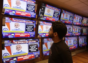 A man watches prime minister Narendra Modi address the nation in a televised speech about Covid-19 situation in India