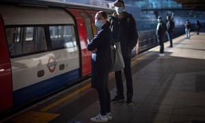 People wearing face masks while waiting for the tube