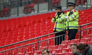 British police officers stand on duty at Wembley stadium as France's players train on the pitch ahead of their international friendly football match against England on 17 November.