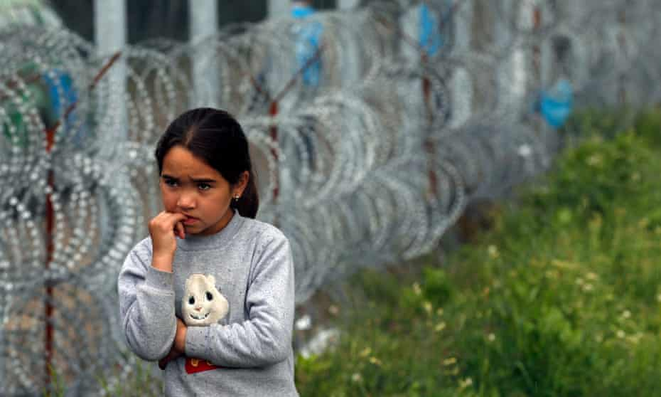 A girl stands near a fence in a makeshift refugee camp at the Horgoš border between Hungary and Serbia.