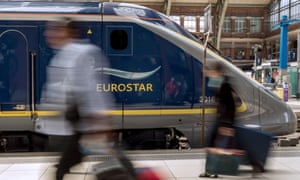 Travellers walk past a Eurostar train at Lille train station.