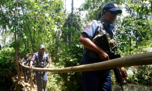 Filipino policemen cross a wooden bridge during a military offensive in the southern Philippines on 27 April.